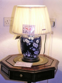 Dark blue jar lamp with white blossom including round pleated shade